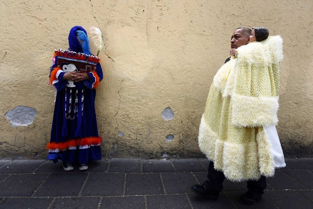 A traditional Chinelo (L) costumed dancer looks on as a man walks by with a dressed-up doll representing the baby Jesus during a celebration 40 days after the birth of Jesus, in Xochimilco on the outskirts of Mexico City, February 2, 2015. (Photo by Edgard Garrido/Reuters)