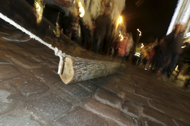 People participate in the ancient Yule Log dragging tradition during winter solstice celebrations in Riga, Latvia, December 21, 2015. (Photo by Ints Kalnins/Reuters)