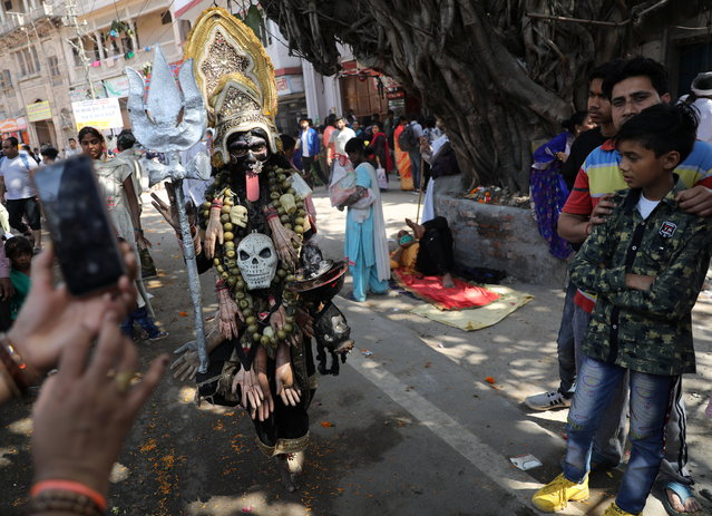 """A woman dressed as Goddess Kali seeks for alms on a street during the first Shahi Snan at """"Kumbh Mela"""", or the Pitcher Festival, in Haridwar, India, March 11, 2021. (Photo by Anushree Fadnavis/Reuters)"""