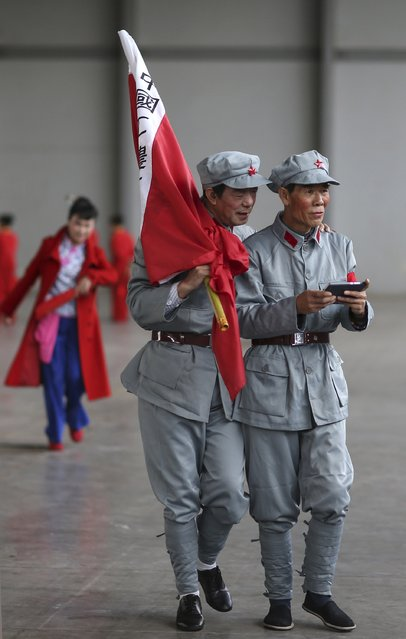 Participants dressed as Red Army soldiers look at a mobile phone as they wait backstage before their performance at a line dancing competition in Kunming, Yunnan province January 31, 2015. Hundreds of residents in about 60 dancing groups attended the competition which kicked off on Saturday and will last for eight days, local media reported. (Photo by Reuters/Stringer)
