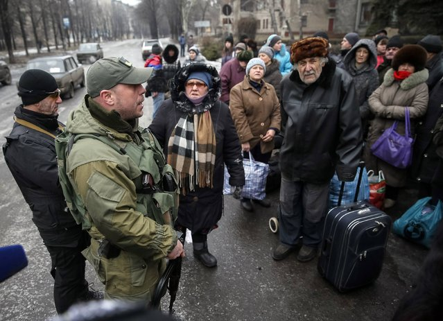 Local residents listen to Ukrainian serviceman as they wait for a bus to flee the conflict in Debaltseve, eastern Ukraine, February 6, 2015. (Photo by Gleb Garanich/Reuters)