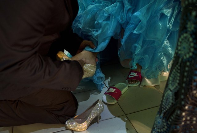 In this December 20, 2015 photo, Ivan Santos removes the sandals of his daughter Daniela Santos Torres as part of a tradition in which fathers place heeled shoes on their daughters during her quinceanera party in the town of Punta brava near  Havana, Cuba. (Photo by Ramon Espinosa/AP Photo)
