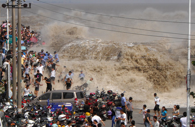 A crowd of Chinese tourists run away as a tidal bore breaks through the dam by the Qiangtang River in Haining, east China's Zhejiang province on August 31, 2011. Visitors gather to experience the Qianjiang Tidal Bore from early morning, an annual tradition for the residents living nearby. (Photo credit should read STR/AFP Photo)
