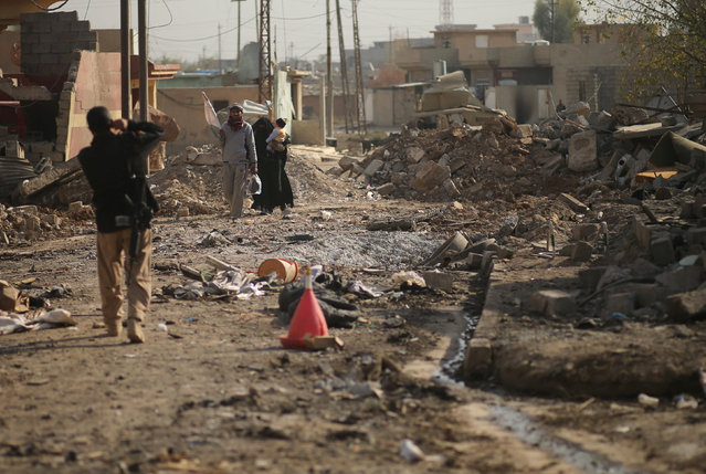 Displaced Iraqis cross makeshift army roadblocks in the frontline neighbourhood of Intisar, eastern Mosul November 27, 2016. (Photo by Mohammed Salem/Reuters)