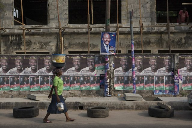 A woman walks past electoral campaign posters in Lagos, February 12, 2015. (Photo by Joe Penney/Reuters)