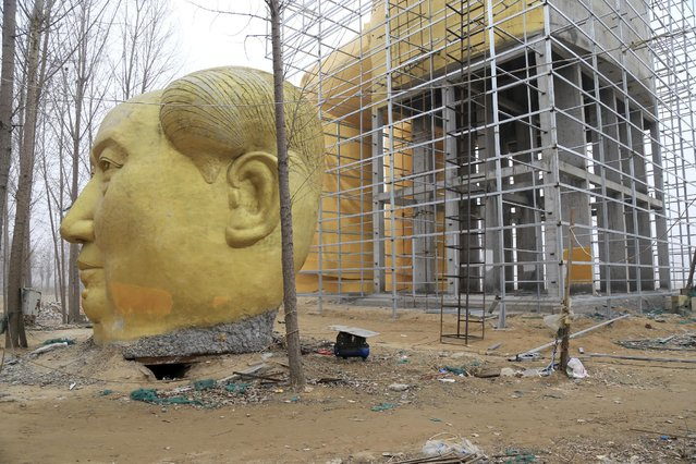 A discarded head is placed on the ground next to a giant statue of Chinese late chairman Mao Zedong under construction near crop fields in a village of Tongxu county, Henan province, China, January 4, 2016. (Photo by Reuters/Stringer)