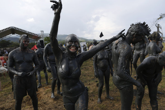"A woman, covered in mud, dances during the traditional ""Bloco da Lama"" or ""Mud Block"" carnival party, in Paraty, Brazil, Saturday, February 14, 2015. Revelers in the seaside colonial town threw themselves into deposits of black, mineral-rich slime, emerging covered head-to-toe in the sludge. Bikinis and trunks disappeared beneath the mud, which highlights both gym-pumped pectorals and beer-fed guts. (Photo by Leo Correa/AP Photo)"