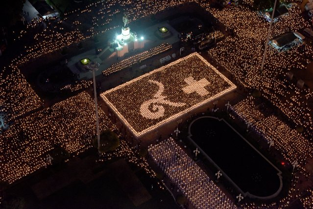 Thai people and nurses from a hospital light candles in formation showing Thai script showing numbers representing the late Thai King Bhumibol Adulyadej (L) at a park in Bangkok on November 30, 2016. Thailand's cabinet on November 29 submitted the name of Crown Prince Maha Vajiralongkorn to the nation's rubber-stamp parliament, paving the way for his endorsement as king several weeks after his father's death. (Photo by Tang Chhin Sothy/AFP Photo)