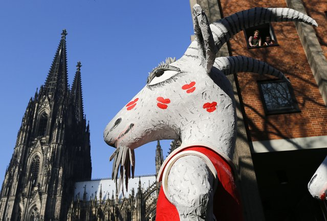 A carnival float of Germany's first soccer division Bundesliga team FC Cologne with its famous goat mascot passes the UNESCO world heritage, the Cologne Cathedral during the traditional Rose Monday carnival parade February 16, 2015. (Photo by Wolfgang Rattay/Reuters)
