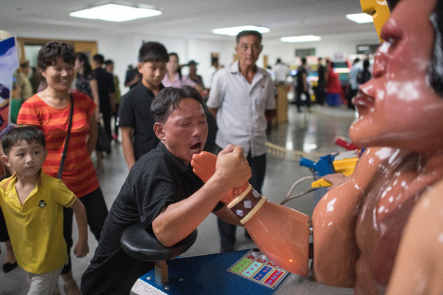 North Koreans look on as a man plays an arm wrestling game in an amusement arcade at Kaeson Youth Park on August 19, 2018 in Pyongyang, North Korea. (Photo by Carl Court/Getty Images)