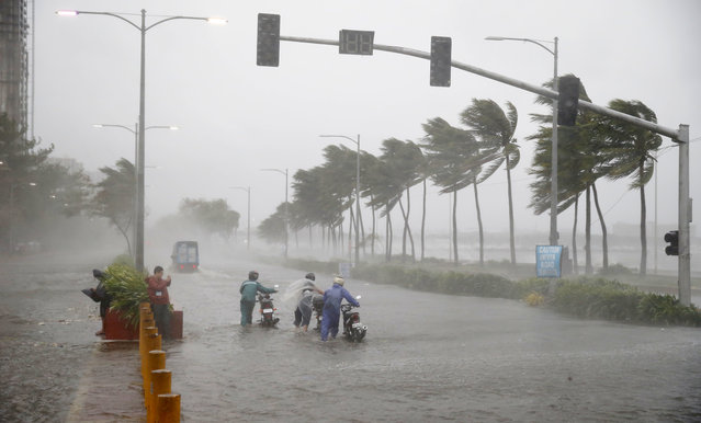 Motorists brave the rain and strong winds brought about by Typhoon Mangkhut which barreled into northeastern Philippines before dawn Saturday, September 15, 2018 in Manila, Philippines. (Photo by Bullit Marquez/AP Photo)