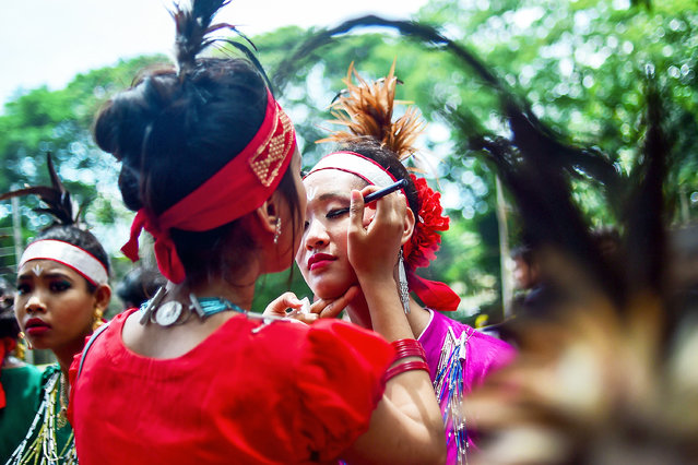 A Bangladeshi indigenous woman helps a dancer with her make-up during a gathering in Dhaka on August 9, 2018, held to celebrate United Nations' (UN) International Day of the World's Indigenous People. (Photo by Munir Uz Zaman/AFP Photo)