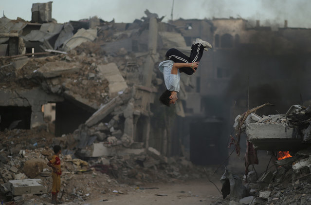 A Palestinian youth practices his Parkour skills over the ruins of houses, which witnesses said were destroyed during a seven-week Israeli offensive, in the Shejaia neighborhood east of Gaza City, October 1, 2014. (Photo by Mohammed Salem/Reuters)