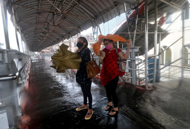 Women take shelter at a pedestrian overpass during heavy rains caused by Cyclone Tauktae in Mumbai, India, May 17, 2021. (Photo by Niharika Kulkarni/Reuters)