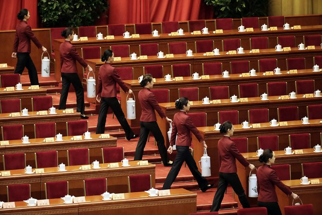 Attendants carry thermos as they prepare tea for delegates ahead of the opening session of Chinese People's Political Consultative Conference (CPPCC) at the Great Hall of the People in Beijing March 3, 2015. REUTERS/Jason Lee