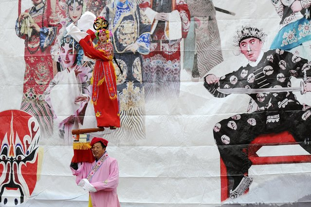 """Performers walk past a poster during """"Shehuo"""" festival before Chinese Lunar New Year, in Hancheng, Shaanxi Province, China, January 16, 2016. (Photo by Reuters/Stringer)"""