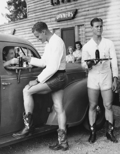 Bowing to the demands of Dallas women who object to girl car-hops in shorts, one large roadside stand, hired four six-footers garbed in shorts and cowboy boots in Dallas, Texas, April 27, 1940. Above Joe Wilcox serves Pauline Taylor, who smiles her approval of the idea. Bound for another car is James Smith at right. (Photo by AP Photo)