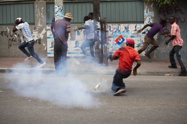 Demonstrators run away from tear gas grenade during a street protest after it was announced that the runoff Jan. 24, presidential election had been postponed, in Port-au-Prince, Haiti, Friday, January 22, 2016. (Photo by Dieu Nalio Chery/AP Photo)