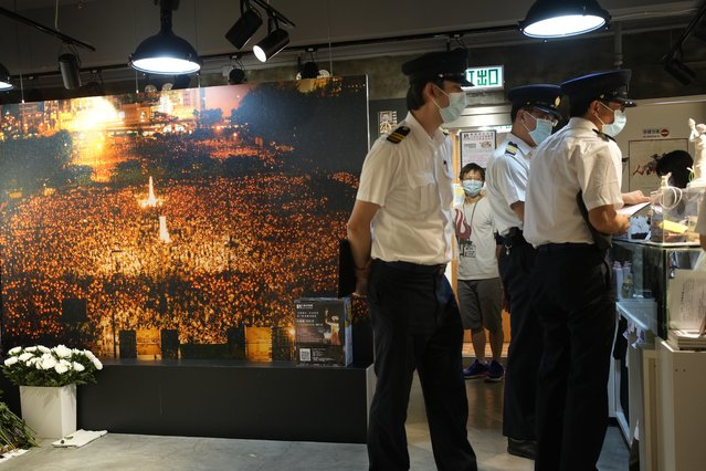"""Officers from Food and Environmental Hygiene Department ask questions to staff next to a huge photo of candlelight vigil at the """"June 4 Memorial Museum"""" run by The Hong Kong Alliance in Support of Patriotic Democratic Movements of China in Hong Kong Tuesday, June 1, 2021. The Hong Kong museum commemorating the bloody crackdown in Tiananmen Square in 1989 has been shut down days after its opening, as authorities continue to crack down on activities related to the event. The museum, which opened on Sunday and was meant to last until June 4, was closed on Wednesday by the organizers after authorities investigated the venue for not having the relevant licenses required for public exhibition. (Photo by Vincent Yu/AP Photo)"""