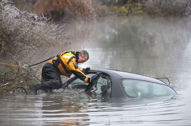A Lane County Sheriffs deputy works to remove a car that crashed in the Maxwell pond on Northwest Express Way in Eugene, Ore., Thursday, December 15, 2016. (Photo by Collin Andrew/The Register-Guard via AP Photo)