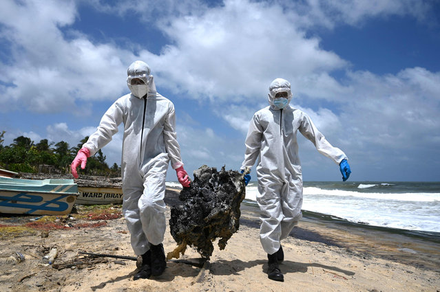 Sri Lanka's Air force personnel remove debris washed ashore from the Singapore-registered container ship MV X-Press Pearl, which has been burning for the eleventh consecutive day in the sea off Sri Lanka's Colombo Harbour, on a beach in Colombo on May 30, 2021. (Photo by Lakruwan Wanniarachchi/AFP Photo)