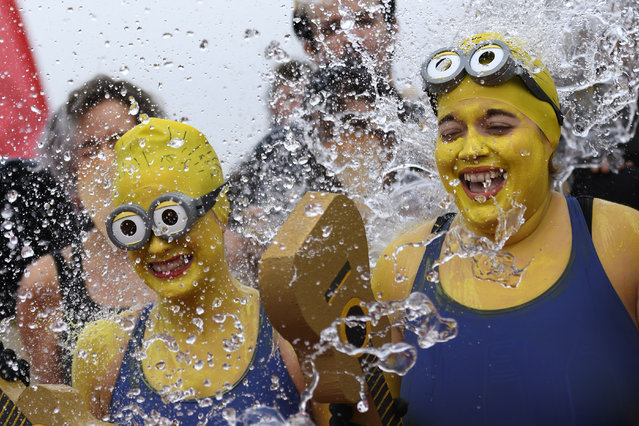 "Women disguised as Minions movie characters take part in the 78th ""Coupe de Noel"" (Christmas cup) swimming race in the Lake Geneva, on December 18, 2016 in Geneva. More than 1800 participants took part in the event, a 12-meter-long swimming off the Geneva's bank in the 7 degrees Celsius cold water. (Photo by Fabrice Coffrini/AFP Photo)"