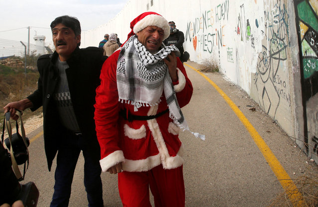 A Palestinian protester, dressed as Santa Claus, reacts after inhaling tear gas fired by Israeli troops during clashes in the West Bank city of Bethlehem December 23, 2016. (Photo by Mussa Qawasma/Reuters)