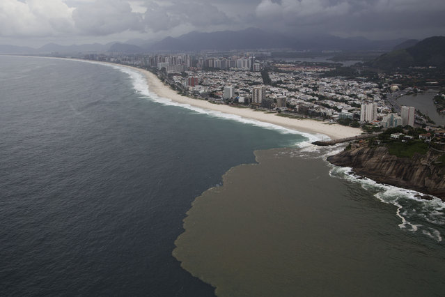 """This aerial view shows polluted water flowing from the Barra channel to the Barra beach, in Rio de Janeiro, Brazil, Monday, March 23, 2015. Rio de Janeiro's mayor acknowledged in a television interview Monday that the run-up to the 2016 games has proven a """"wasted opportunity"""" to clean up the city's blighted waterways. (Photo by Felipe Dana/AP Photo)"""
