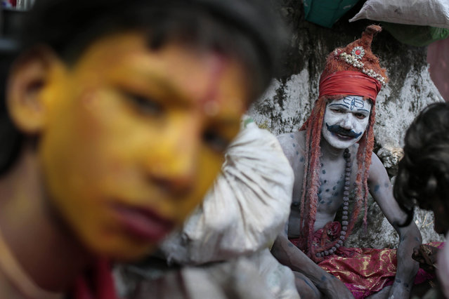 A Bangladeshi Hindu devotee dressed as Hindu God Shiva sits on the banks of the Brahmaputra river during a Hindu bathing ritual in Langalbandh, 20 kilometers (12 miles) southeast of capital Dhaka, Bangladesh, Friday, March 27, 2015. Local police chief Nazrul Islam said a stampede took place in a Hindu pilgrimage spot on the banks of the Brahmaputra river during an annual religious bathing ritual. (Photo by A. M. Ahad/AP Photo)