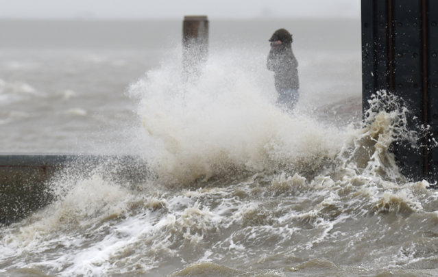 A stroller walks on a pier as waves of the Northern Sea crash against it in Dagebuell, northern Germany, Tuesday, March 31, 2015. (Photo by Carsten Rehder/AP Photo/DPA)