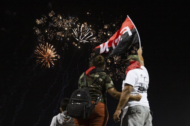 Supporters of the Sandinista National Liberation Front (FSLN) watch fireworks during commemorations for the 42nd anniversary of the triumph of the 1979 Sandinista Revolution that toppled dictator Anastasio Somoza in Managua, Nicaragua, early Monday, July 19, 2021. (Photo by Miguel Andrés/AP Photo)