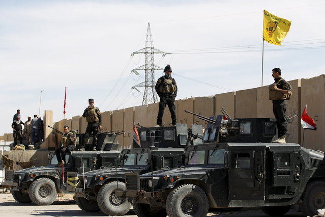 Iraqi security forces stand on their military vehicles in Tikrit, March 27, 2015. (Photo by Thaier Al-Sudani/Reuters)