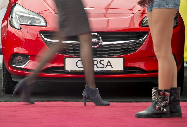 A woman walks by an Opel Corsa automobile, on display at the Bucharest Auto Moto Show in Bucharest, Romania, Thursday, April 2, 2015. The show displays mostly brands on sale in the Romanian market.(Photo by Vadim Ghirda/AP Photo)