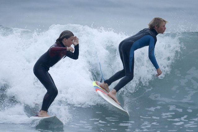 Shane Moseley, 13, (L) and Carlos Price Gracida, 13, surf before school at sunrise in Hermosa Beach, California March 31, 2015. (Photo by Lucy Nicholson/Reuters)