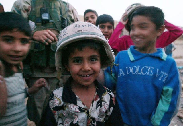 An Iraqi child wears a helmet from the U.S. Marine Expeditionary Unit Fox Company as they push into southern Iraq to take control of the main port of Umm Qasr, March 2003. (Photo by Desmond Boylan/Reuters)