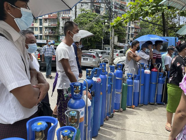 People queue up with their oxygen tanks outside an oxygen refill station in Pazundaung township in Yangon, Myanmar, Sunday, July 11, 2021. Myanmar is facing a rapid rise in COVID-19 patients and a shortage of oxygen supplies just as the country is consumed by a bitter and violent political struggle since the military seized power in February. (Photo by AP Photo/Stringer)