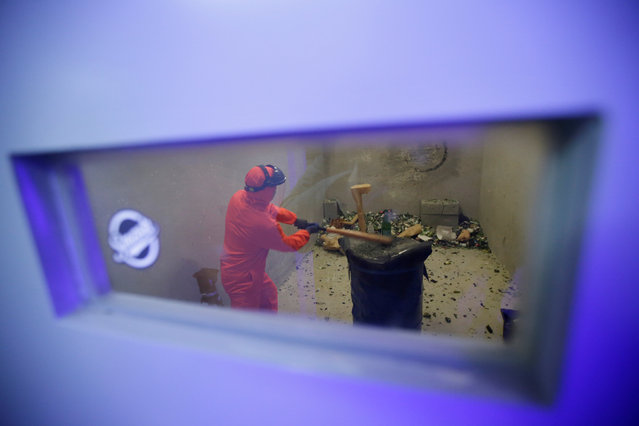 Customer Liu Chao, wearing protective gear, is seen through a window as he smashes bottles in an anger room in Beijing, China January 12, 2019. (Photo by Jason Lee/Reuters)