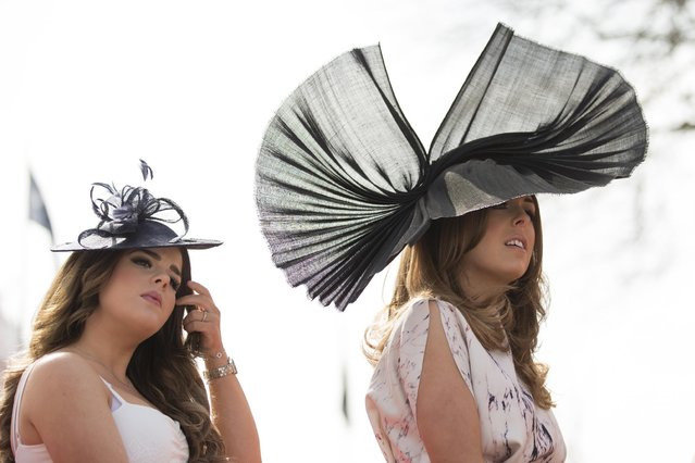 Spectators await the start of racing during Aintree race meeting's Ladies Day the day before the Grand National horse race at Aintree Racecourse Liverpool, England, Friday, April 10, 2015. (Photo by Jon Super/AP Photo)