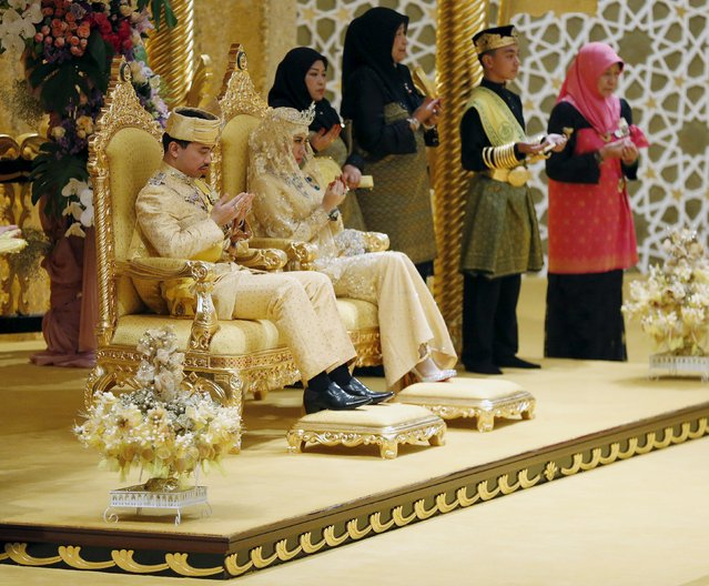 "Brunei's newly wed royal couple, Prince Abdul Malik and Dayangku Raabi'atul 'Adawiyyah Pengiran Haji Bolkiah, pray during the ""bersanding"" or enthronement ceremony at their wedding in the Nurul Iman Palace in Bandar Seri Begawan April 12, 2015. (Photo by Olivia Harris/Reuters)"