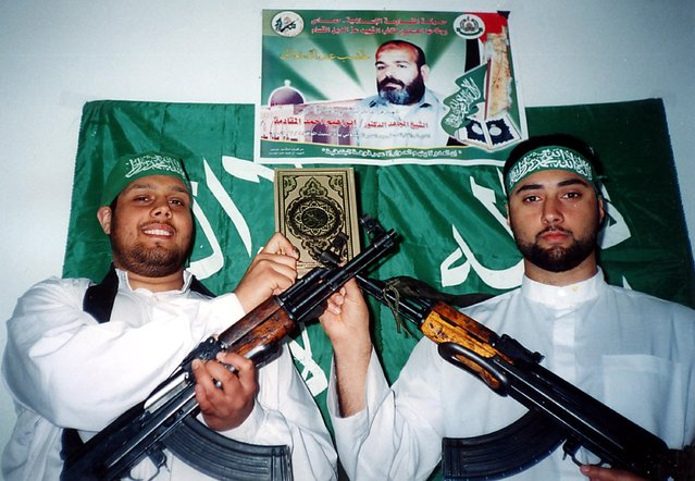 In this frame grab handout image released March 8, 2004 by Hamas nearly a year after their deaths, British Muslim suicide bombers, 27-year-old Omar Khan Sharif (R) and 22-year-old Asif Muhahmmad Hanif stand together in uniform as they hold AK 47 rifles, and stand together under a poster of Hamas leader Ibrahim al-Maqadmehin, February 8, 2003 in Gaza Strip. (Photo via Getty Images)