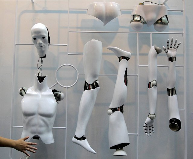 """A visitor waves in front of the sensor that triggers the joints of a dummy that is part of """"PWM1"""", an art creation by Taiwan artist Huang Zan-lun, during the Art Taipei 2010 in this August 20, 2010 file photo. (Photo by Pichi Chuang/Reuters)"""