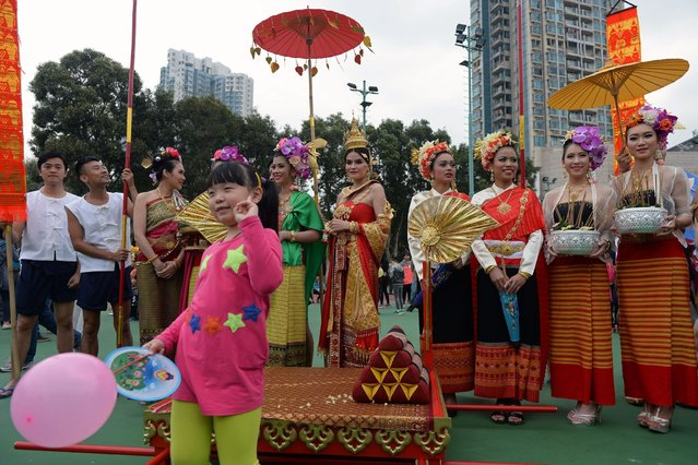 A child poses for a photograph in front of performers after a parade to celebrate the Songkran festival in Hong Kong on April 12, 2015. The Songkran festival marks the start of the traditional new year in Thailand which begins on April 13. (Photo by Dale de la Rey/AFP Photo)