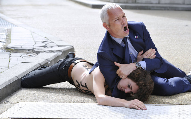 A security guard tackles to the ground a Femen activist as she tried along with two other feminist activists to stop the car of Tunisian Prime Minister from leaving the EU commission building after his working session with European Commission President on June 25, 2013 at the EU headquarters in Brussels. (Photo by Georges Gobet/AFP Photo)