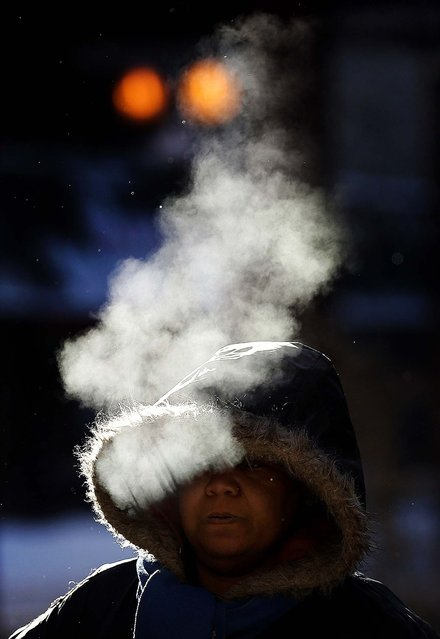 A woman walks in frigid cold temperatures though downtown Chicago on Monday. (Photo by Jim Young/Reuters)