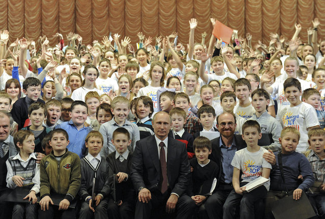 Russian President Vladimir Putin (C) poses for a picture with members of a children's choir during his visit to the Mariinsky Theatre in St.Petersburg January 7, 2014. (Photo by Mikhail Klimentyev/Reuters/RIA Novosti/Kremlin)