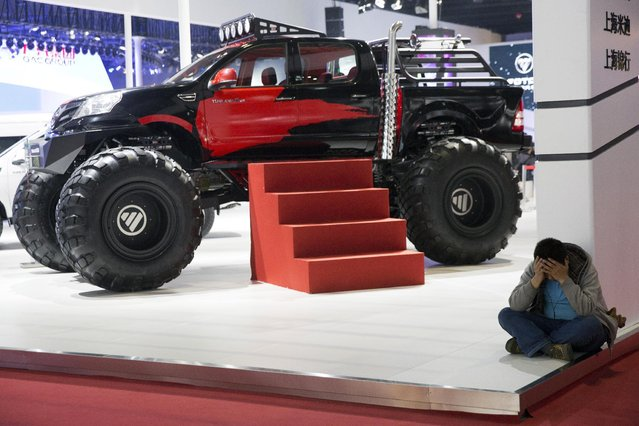 A man rests near an oversized truck displayed at the Shanghai Auto Show in Shanghai, Monday, April 20, 2015. (Photo by Ng Han Guan/AP Photo)