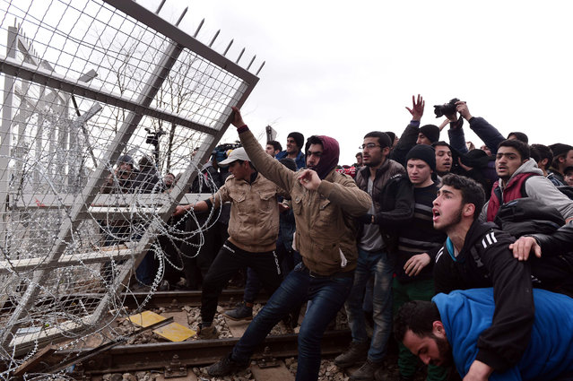 "Refugees break into the Greek-Macedonian borders during their protest demanding the opening of the borders near the village of Idomeni on February 29, 2016. Macedonian police fired tear gas on February 29, 2016, as a group of some 300 Iraqi and Syrians forced their way through a Greek police cordon and raced towards a railway track between the two countries. With Austria and Balkan states capping the numbers of migrants entering their soil, there has been a swift buildup along the Greece-Macedonia border with Athens warning that the number of people ""trapped"" could reach up to 70,000 by next month. (Photo by Louisa Gouliamaki/AFP Photo)"