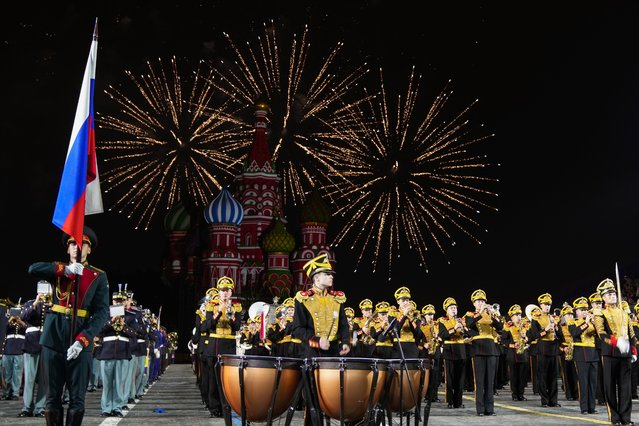 Fireworks explode as a combined military band of the participating countries performs during the Spasskaya Tower International Military Music Festival in Red Square, with the St. Basil Cathedral in the background, in Moscow, Russia, Tuesday, August 31, 2021. (Photo by Pavel Golovkin/AP Photo)