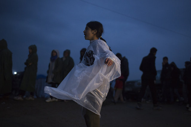 A girl wearing a  plastic rain poncho walks as refugees and migrants wait to receive food distributed by non-governmental organization at the Greek-Macedonian border, in the northern Greek village of Idomeni, on Monday, February 29, 2016. (Photo by Petros Giannakouris/AP Photo)