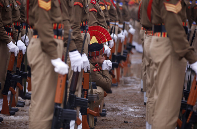 An Indian policeman blows warm air onto his hand as he takes part in a parade to celebrate India's Republic Day on a cold winter day in Srinagar January 26, 2017. (Photo by Danish Ismail/Reuters)